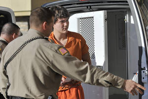 Photo - Tanner Vanpelt, a suspect in a triple homicide in Clark, Wyo., is led into the Park County Courthouse in Cody for his arraignment Tuesday, March 5, 2013.  Vanpelt, 18, and Stephen Hammer, 19, are charged with 11 felony counts, including premeditated murder, use of a deadly weapon and robbery. Some of the charges could carry the death penalty.   Hammer and Vanpelt were arrested after neighbors described two men entering a house Saturday where the victim's bodies were found. The neighbors saw two vehicles speeding away, including a black Audi belonging to Ildiko Freitas, 40, who owned the house with her husband. Freitas and her parents, Janos Volgyesi, 69, and Hildegard Volgyesi, 70, were found dead inside the house. (AP Photo/Billings Gazette, James Woodcock)