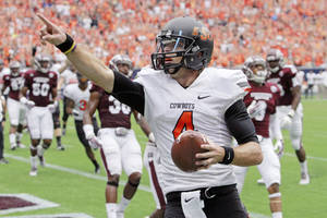 Photo - Oklahoma State quarterback J.W. Walsh points to the stands as he scores a touchdown against Mississippi State during the first half of an NCAA college football game,  Saturday, Aug. 31, 2013, in Houston. (AP Photo/Richard Carson)