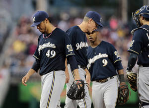 Photo - Milwaukee Brewers starting pitcher Yovani Gallardo (49) walks off the mound after being taken out by Milwaukee Brewers manager Ron Roenicke, second from left, during the fourth inning of a baseball game against the Washington Nationals at Nationals Park Monday, July 1, 2013, in Washington. (AP Photo/Alex Brandon)