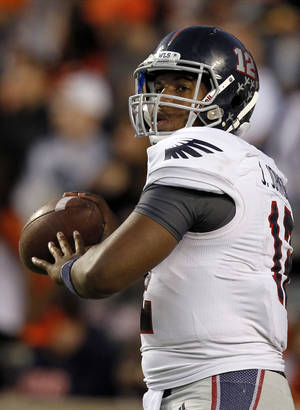 Photo - Florida Atlantic quarterback Jaquez Johnson warms up before the first half of an NCAA college football game against Auburn on Saturday, Oct. 26, 2013, in Auburn, Ala. (AP Photo/Butch Dill)