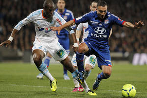 photo - Marseille's Rod Fanni, left, challenges for the ball with Lyon's Steed Malbranque during their French League One soccer match at Gerland stadium, in Lyon, central France, Sunday, March 10, 2013. (AP Photo/Laurent Cipriani)
