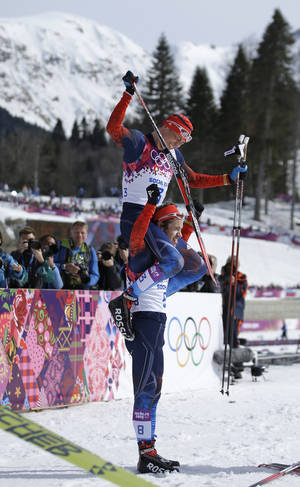 Photo - Russia's Alexander Legkov, the gold medal winner, is carried on the shoulders of bronze medalist Russia's Ilia Chernousov after the men's 50K cross-country race at the 2014 Winter Olympics, Sunday, Feb. 23, 2014, in Krasnaya Polyana, Russia. (AP Photo/Gregorio Borgia)