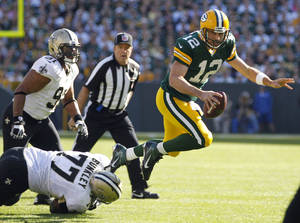Photo -   Green Bay Packers quarterback Aaron Rodgers gets tripped up by New Orleans Saints defensive tackle Brodrick Bunkley as defensive end Will Smith watches during the first half of an NFL football game Sunday, Sept. 30, 2012, in Green Bay, Wis. (AP Photo/Mike Roemer)