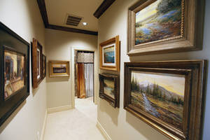 Photo - Framed art work lines a hallway at 1401 NW 158, one of three new houses in the Symphony Show House fundraiser. <strong>PAUL HELLSTERN - The Oklahoman</strong>
