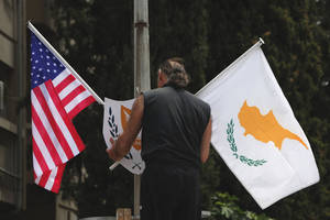 Photo - A municipality worker places a US flag, left  and Cypriot flag,  on an electricity column, on a street in divided capital Nicosia, Cyprus, Tuesday, May 20, 2014. US Vice President Joe Biden arrives in Cyprus Wednesday for an official, three-day visit to the ethnically divided island. Energy prospects in the east Mediterranean, the situation in Ukraine and talks to reunify Cyprus will top Biden's agenda, who is the most senior American official to visit the island in 52 years. (AP Photo/Petros Karadjias)