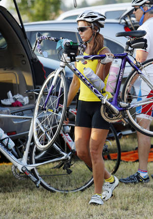 Photo - Jennifer Sullivan, of Edmond, carries her bike Saturday to the start of the Norman Conquest bicycle ride.