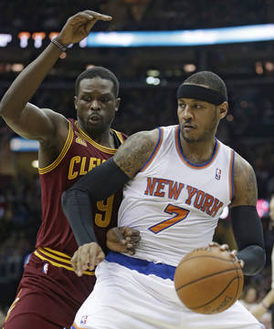 Photo - New York Knicks' Carmelo Anthony (7) drives past Cleveland Cavaliers' Luol Deng, (9) during the first quarter of an NBA basketball game Saturday, March 8, 2014, in Cleveland. (AP Photo/Tony Dejak)