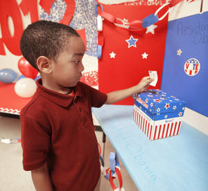 Photo - Capitol Hill Elementary kindergartner Jiren Garett cast his vote in Oklahoma City, Wednesday October 31, 2012. Photo By Steve Gooch, The Oklahoman