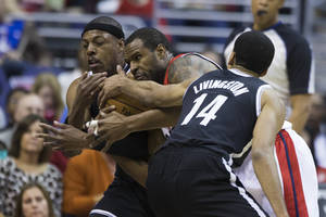 Photo - Brooklyn Nets forward Paul Pierce, left, and teammate guard Shaun Livingston, right, try to take the ball away from Washington Wizards forward Trevor Booker during the first half of an NBA basketball game on Saturday, March 15, 2014, in Washington. (AP Photo/ Evan Vucci)
