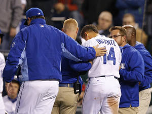 Photo - Kansas City Royals manager Ned Yost, left, comforts Omar Infante (14) as trainers help him from the field during the seventh inning of the MLB American League baseball game against the Tampa Bay Rays at Kauffman Stadium in Kansas City, Mo., Monday, April 7, 2014. Infante was hit by a pitch from Tampa Bay Rays relief pitcher Heath Bell. The Royals defeated the Rays 4-2. (AP Photo/Orlin Wagner)