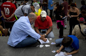 Photo - People exchange stickers of soccer players to complete their World Cup sticker albums at a meeting of collectors in Caracas, Venezuela, Saturday, June 21, 2014. Adults and children alike are spilling into plazas around the country to swap and buy business card-sized stickers with the faces of players and photos of Brazilian stadiums. (AP Photo/Ramon Espinosa)