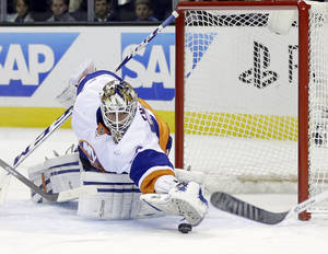 Photo - New York Islanders goalie Kevin Poulin stops a shot against the San Jose Sharks during the first period of an NHL hockey game on Tuesday, Dec. 10, 2013, in San Jose, Calif. (AP Photo/Marcio Jose Sanchez)
