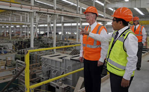Photo - In this Aug. 29, 2013 photo provided by the Alabama Governor's office, Gov. Robert Bentley, left, listens to Roger Zhang, Golden Dragon U.S.A. President, during a tour of the new Golden Dragon copper tubing plant, then under construction, in Pine Hill, Ala. Golden Dragon, the first company Bentley recruited to Alabama after being elected, will employ 300 new full-time employees in rural Wilcox County. (AP Photo/Alabama Governor's Office, Jamie Martin)