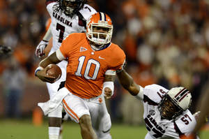 Photo -   Clemson quarterback Tajh Boyd (10) avoids the tackle of South Carolina's Aldrick Fordham (57) during the first half of an NCAA college football game on Saturday, Nov. 24, 2012, at Memorial Stadium in Clemson, S.C. (AP Photo/Richard Shiro)