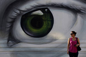 Photo - A woman waits to cross the road in front of a mural of an eye in Athens, on Friday, Sept. 6, 2013. (AP Photo/Petros Giannakouris)