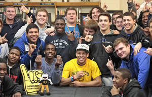 "Photo - Football player Kai Callins, center in yellow, hold up the ""Singers Up"" sign with his teammates at Guthrie High School, Wednesday, February 4, 2014. PHOTO BY DAVID McDANIEL, The Oklahoman <strong>David McDaniel</strong>"