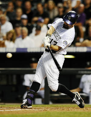 Photo - Colorado Rockies' Todd Helton hits a home run in the second inning of a baseball game against the Los Angeles Dodgers, Wednesday, Sept. 4, 2013, in Denver. (AP Photo/Chris Schneider)