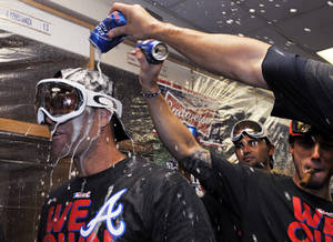 Photo - Atlanta Braves' Tim Hudson, left, celebrates with teammates after the Braves clinched the NL East title with a 5-2 win over the Chicago Cubs in a baseball game in Chicago, Sunday, Sept. 22, 2013. (AP Photo/David Banks, Pool)