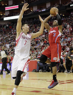 Photo - Los Angeles Clippers guard Chris Paul (3) shoots over Houston Rockets guard Jeremy Lin (7) during the first half of an NBA basketball game Saturday, March 30, 2013 in Houston. (AP Photo/Bob Levey)