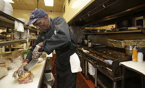 Photo - In this Friday, June 6, 2014 photo, executive chef Raymond Nicholson cuts a corned beef reuben sandwich at Corky & Lenny's Restaurant & Deli in Woodmere Village, Ohio. The Commerce Department releases first-quarter gross domestic product on Wednesday, June 25, 2014. (AP Photo/Tony Dejak)