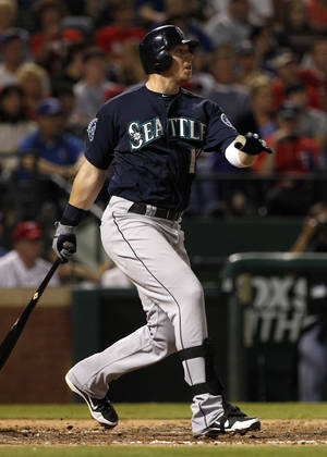 Photo -   Seattle Mariners' Justin Smoak follows through on a single off of Texas Rangers' Scott Feldman, scoring Michael Saunders, in the third inning of a baseball game Saturday, Sept. 15, 2012, in Arlington, Texas. (AP Photo/Tony Gutierrez)