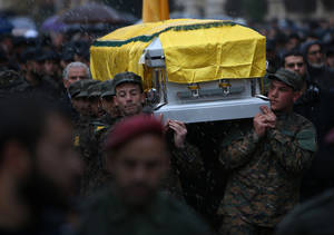 Photo - Hezbollah fighters carry the coffin of Hassan al-Laqis, a senior commander for the Lebanese militant group Hezbollah, who was gunned down outside his home, during his funeral procession at his hometown in Baalbek city, east Lebanon, Wednesday, Dec. 4, 2013. The assassination was a major breach of the Shiite militant group's security as it struggles to maintain multiple fronts while it fights alongside President Bashar Assad's forces in Syria. (AP Photo/Hussein Malla)
