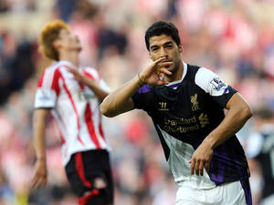 Photo - Liverpool's Luis Suarez celebrates after scoring his goal during their English Premier League soccer match against Sunderland at the Stadium of Light, Sunderland, England, Sunday, Sept. 29, 2013. (AP Photo/Scott Heppell)l)