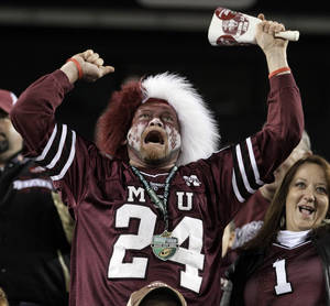 Photo - A Mississippi State fan rings a cowbell as he cheers on against Wake Forest during the fourth quarter of the Music City Bowl NCAA college football game on Friday, Dec. 30, 2011, in Nashville, Tenn. Mississippi State won 23-17. (AP Photo/Mark Humphrey) ORG XMIT: TNMH120