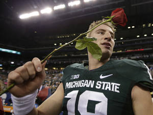 Photo - Michigan State's Connor Cook holds a rose after Michigan State defeated Ohio State, 34-24 in the Big Ten Conference championship NCAA college football game Saturday Dec. 7, 2013, in Indianapolis. (AP Photo/AJ Mast)