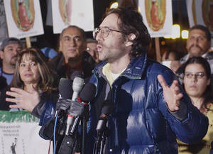 Photo - FILE - Dov Charney, senior partner of American Apparel, announces he will shutter his garment manufacturing plant that employs some 1,500 workers, in observance of a scheduled Dec. 12 economic strike by Latinos, at a rally at Los Angeles' downtown Plaza in this Dec. 11, 2003 file photo. The board of American Apparel voted to oust founder Dov Charney as chairman and notified him of its intent to remove him as president and chief executive, the clothing chain said in a statement Wednesday night June 18, 2014. (AP Photo/Reed Saxon, File)