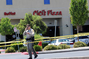 Photo - A Las Vegas police officer walks near the scene of a shooting in Las Vegas, Sunday, June 8, 2014. The spree began around 11:30 a.m. Sunday when a man and woman walked into CiCi's Pizza and shot two officers who were eating lunch, Las Vegas police spokesman Larry Hadfield said. (AP Photo/Las Vegas Review-Journal, Eric Verduzco)