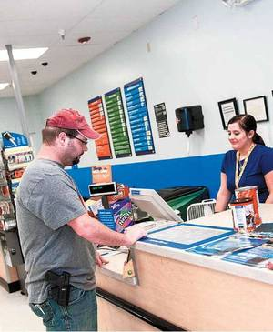 Photo - Hunter Brown talks with Darla McMahon in the automotive section of Walmart. Photo by Brett Roho for the Tulsa World