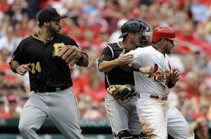 Photo - St. Louis Cardinals' Yadier Molina, right, is tagged out by Pittsburgh Pirates catcher Tony Sanchez, center, after being caught between third and home as Pirates third baseman Pedro Alvarez, left, watches during the second inning of a baseball game on Sunday, April 27, 2014, in St. Louis. (AP Photo/Jeff Roberson)