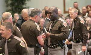 Photo - Oklahoma Highway Patrol troopers receive their badges during their graduation on Friday. This is the first class in more than three years. Photo By David McDaniel/The Oklahoman <strong>David McDaniel - The Oklahoman</strong>