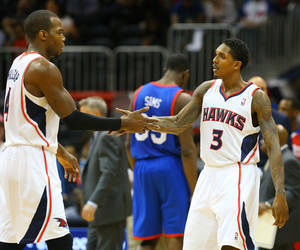 Photo - Atlanta Hawks guard Lou Williams, right, celebrates hitting one of his three-pointers down the stretch with teammate Paul Millsap, left. on the way to a 103-95 victory over the Sixers in an NBA basketball game on Monday, March 31, 2014, in Atlanta.   (AP Photo/Atlanta Journal-Constitution, Curtis Compton)