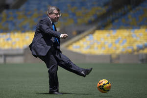 Photo - International Olympic Committee (IOC) President Thomas Bach kicks a soccer ball during a visit to Maracana stadium in Rio de Janeiro, Brazil, Wednesday, Jan. 22, 2014. The city of Rio de Janeiro will host the Olympics in 2016. (AP Photo/Felipe Dana)