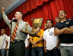 "Photo - Sharing the stage with David Olivas (right) and the rest of the boys soccer team, Principal Chris Brewster leads a ""Saints"" cheer during a pep rally to present Santa Fe South High School with their State Championship trophy in Oklahoma City on Tuesday, May 19, 2009. David Olivas scored both goals during the Saints' win over Cascia Hall in the state championship game last Saturday. Photo by John Clanton, The Oklahoman"