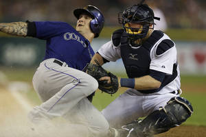 Photo - Colorado Rockies' Brandon Barnes safely slides under the tag of Detroit Tigers catcher Bryan Holaday during the seventh inning of an interleague baseball game, Friday, Aug. 1, 2014, in Detroit. (AP Photo/Carlos Osorio)