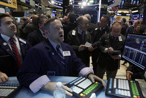 Photo - Specialist Michael Shearin, foreground center, works at his post on the floor of the New York Stock Exchange, Wednesday, Jan. 8, 2014.Stocks are mostly lower in early trading as investors hold back ahead of the release of the latest news from the Federal Reserve. (AP Photo/Richard Drew)