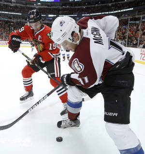 Photo - Chicago Blackhawks center Jonathan Toews (19) and Colorado Avalanche left wing Jamie McGinn battle for a loose puck along the boards during the second period of an NHL hockey game, Tuesday, Jan. 14, 2014, in Chicago. (AP Photo/Charles Rex Arbogast)
