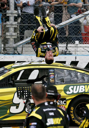 Photo - Carl Edwards performs a flip in front of his crew as he celebrates winning the NASCAR Sprint Cup Series auto race, Sunday, March 3, 2013, in Avondale, Ariz. (AP Photo/Ross D. Franklin)
