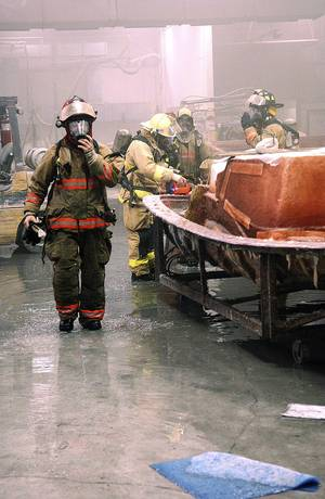 Photo - Miami, OK, firefighters stand in the Tracker Marine Factory in Miami on Monday after putting out a fire that was contained to one part of the factory. Sprinklers flooded the plant and filled it with smoke.  Photo By Gary Crow,  for The Oklahoman