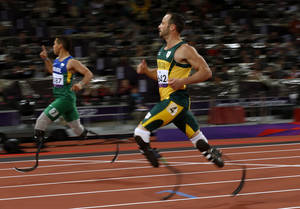 Photo -   Brazil's Alan Fonteles Cardoso Oliveira, left, celebrates after running in to win the gold medal ahead of South Africa's Oscar Pistorius, right, who took the silver medal in the men's 200m T44 category final during the athletics competition at the 2012 Paralympics, Sunday, Sept. 2, 2012, in London. (AP Photo/Matt Dunham)