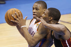 Photo - Oklahoma City's Russell Westbrook (0) drives past Miami's Chris Bosh (1) during Game 2 of the NBA Finals between the Oklahoma City Thunder and the Miami Heat at Chesapeake Energy Arena in Oklahoma City, Thursday, June 14, 2012. Photo by Chris Landsberger, The Oklahoman