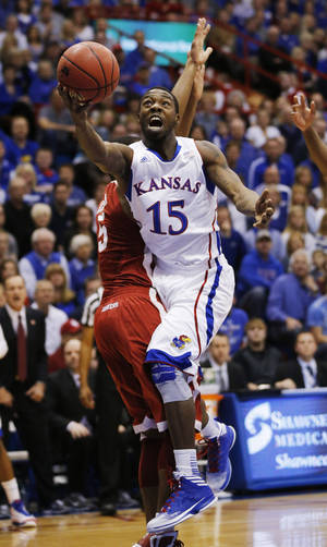 Photo - Kansas guard Elijah Johnson (15) charges into Oklahoma guard Je'lon Hornbeak (5) during the first half of an NCAA college basketball game in Lawrence, Kan., Saturday, Jan. 26, 2013. (AP Photo/Orlin Wagner)