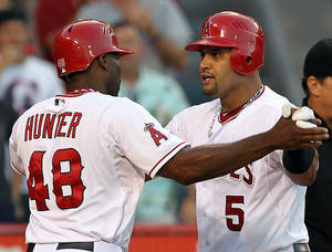 Photo -   Los Angeles Angels' Torii Hunte (48) and Albert Pujols celebrate after scoring on Pujols' home run against the Texas Rangers in the seventh inning of a baseball game in Anaheim, Calif., Sunday, July 22, 2012. (AP Photo/Reed Saxon)