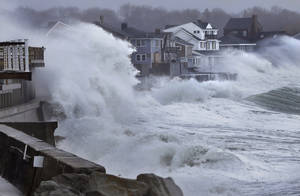 Photo - Ocean waves crash over a seawall and into houses along the coast in Scituate, Mass., Thursday, March 7, 2013. A nor'easter is bringing wind-whipped, wet snow to Massachusetts, and coastal flooding is expected in communities still recovering from February's blizzard. (AP Photo/Steven Senne)