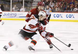 Photo - New Jersey Devils' Patrik Elias (26), of the Czech Republic, gets a pass off as he is hit by Phoenix Coyotes' Tim Kennedy (34) during the first period of an NHL hockey game on Saturday, Jan. 18, 2014, in Glendale, Ariz. (AP Photo/Ross D. Franklin)
