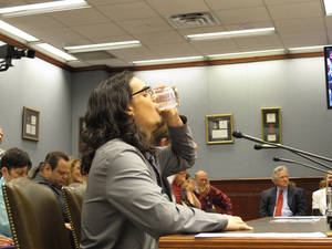 Photo - Dustin Soileau of Lafayette drinks a glass of raw milk after speaking to the House Agriculture Committee on Thursday, April 24, 2014, in Baton Rouge, La. Soileau was supporting a bill to allow Louisiana farms to sell raw milk to consumers. (AP Photo/Melinda Deslatte)