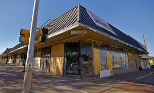 Photo -  Developer Johnathan Russell bought the shopping center at the corner of NW 23 and Walker Avenue unaware that historic facades were hidden under awnings and brick added over the past 40 years. The awning shown in this 2013 photo hid an engraved granite facade. Photo by Chris Landsberger, The Oklahoman  <strong>CHRIS LANDSBERGER -  CHRIS LANDSBERGER </strong>
